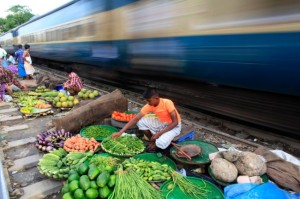A vendor sorts vegetables next to a railway track as a train passes by, in Dhaka on September 10, 2012. (Andrew Biraj/Reuters)