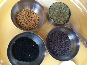 Whole spices clockwise from top left: fenugreek, fennel, mustard, nigella